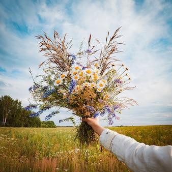 Schönes junges mädchen in einer blumenwiese genießt das aroma und die aussicht von gänseblümchen