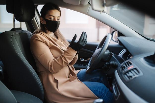Schönes junges mädchen in einer maske, die in einem auto sitzt und schutzhandschuhe anzieht.