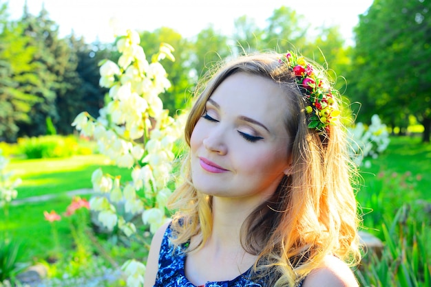 Schönes junges mädchen in einer positiven stimmung, die gegen das helle ewige helle grün im park ruhig ist