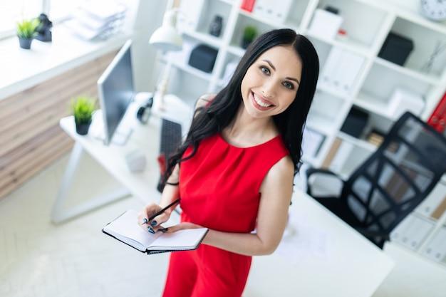 Schönes junges mädchen in einer roten klage steht im büro und hält ein notizbuch und einen bleistift.