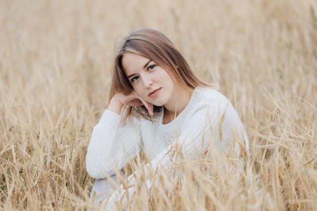 Schönes junges mädchen in einer weißen strickjacke sitzt auf einem weizengebiet.
