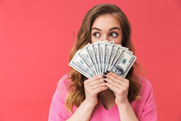 Schönes junges mädchen in freizeitkleidung, das isoliert über rosa wand steht und geldbanknoten zeigt