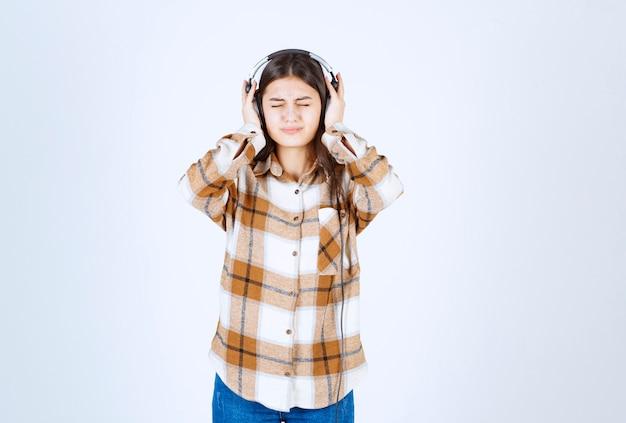 Schönes junges mädchen in kopfhörern, das lied mit lauter lautstärke hört.