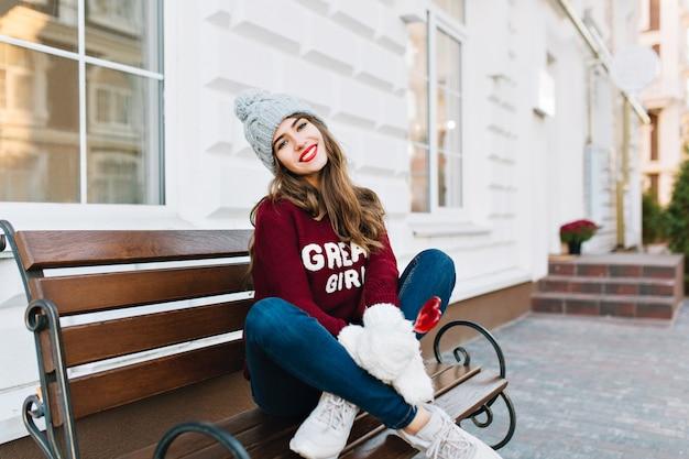 Schönes junges mädchen in voller länge mit langen haaren in strickmütze, jeans und weißen handschuhen, die auf bank auf straße sitzen. sie hält ein karamellherz und lächelt.
