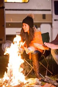Schönes junges mädchen lacht und wärmt sich am lagerfeuer auf einem campingplatz mit retro-wohnmobil im hintergrund.
