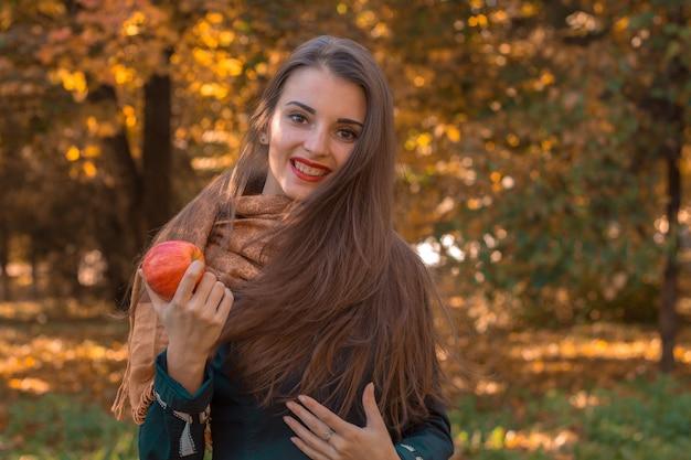 Schönes junges mädchen lächelt und hält einen roten apfel in der hand nahaufnahme