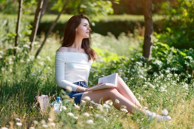 Schönes junges mädchen liest ein buch in einem sommerpark draußen.