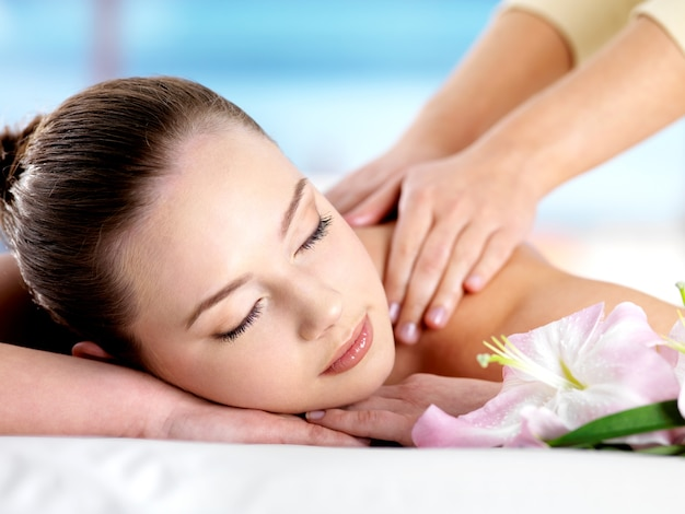 Schönes junges mädchen mit attraktivem gesicht, das eine massage für schulter auf resort - farbigem raum hat