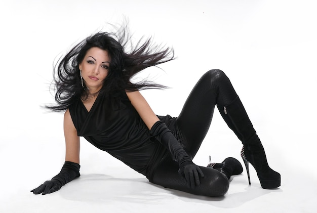 Schönes junges mädchen mit blasendem haar im schwarzen kleid auf weißem hintergrund