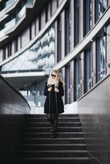 Schönes junges mädchen mit blondem gewelltem haar im schwarzen kleid geht auf ein modernes gebäude