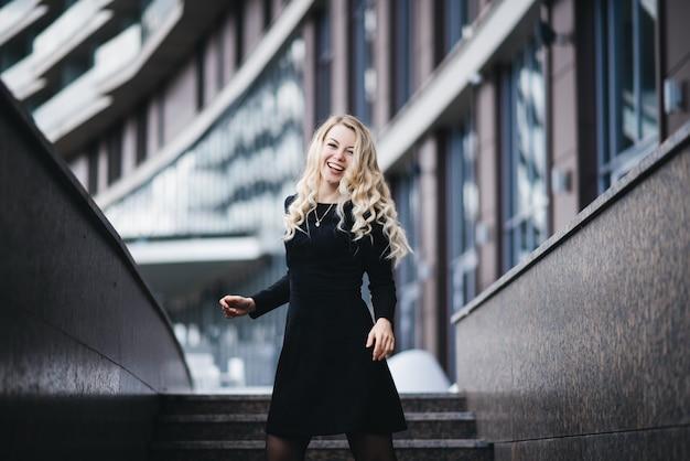 Schönes junges mädchen mit blondem welligem haar im schwarzen kleid, das spaß an einem modernen gebäude hat