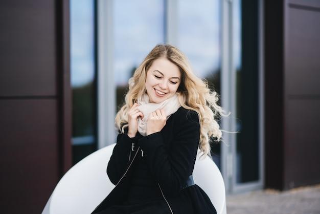 Schönes junges mädchen mit blondem welligem haar in einem schwarzen mantel sitzt auf einem modernen gebäude