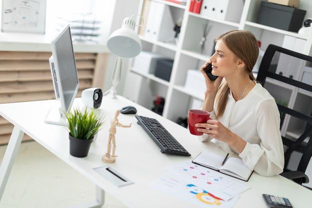 Schönes junges mädchen mit blonden haaren. ein mädchen in einer weißen bluse arbeitet im büro