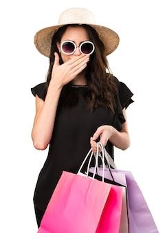 Schönes junges mädchen mit der einkaufstasche, die ihren mund bedeckt