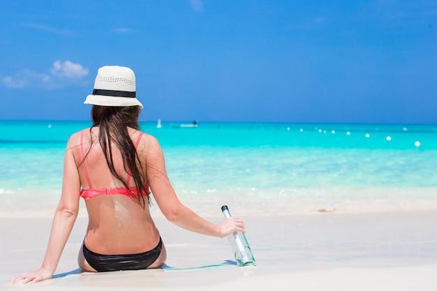 Schönes junges mädchen mit der flasche, die auf dem strand sitzt