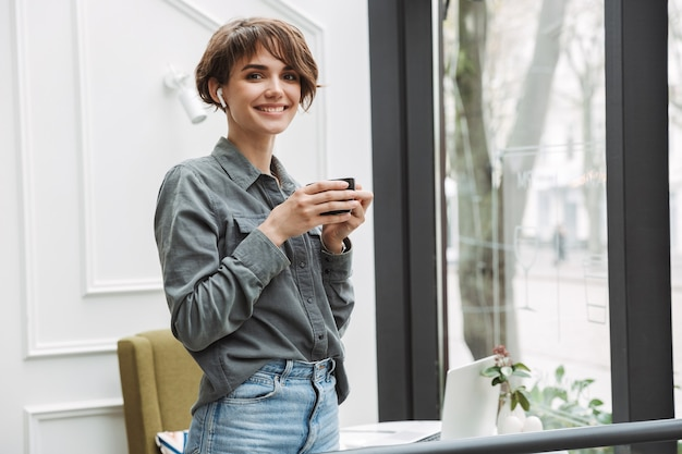 Schönes junges mädchen mit drahtlosen kopfhörern, das kaffee trinkt, während es drinnen im café steht?