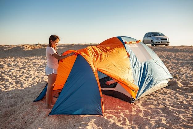 Schönes junges mädchen mit dunklen haaren baut ein zelt am strand auf. autocamping auf einem einsamen sandstrand