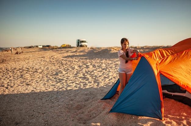 Schönes junges mädchen mit dunklen haaren baut ein zelt am strand auf