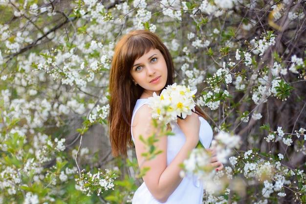 Schönes junges mädchen mit einem blumenstrauß von narzissen in einem weißen kleid