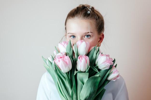 Schönes junges mädchen mit einem bündel frühlingsblumen, frauentag, muttertagsgrußkarte