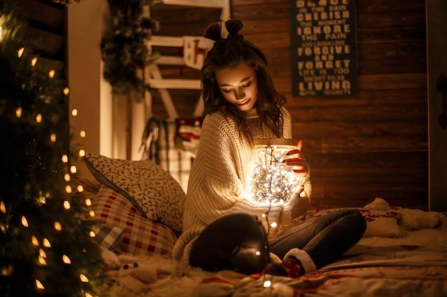 Schönes junges mädchen mit einem haarschnitt in einem weinlese-strickpullover mit einem magischen glas mit feiertagslichtern auf dem bett. heiligabend
