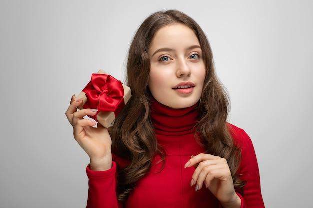 Schönes junges mädchen mit geschenk in der hand