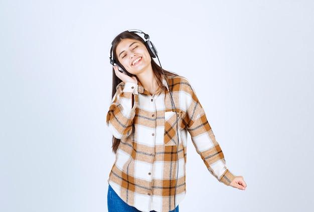 Schönes junges mädchen mit kopfhörern, das lied hört und über weiße wand tanzt.