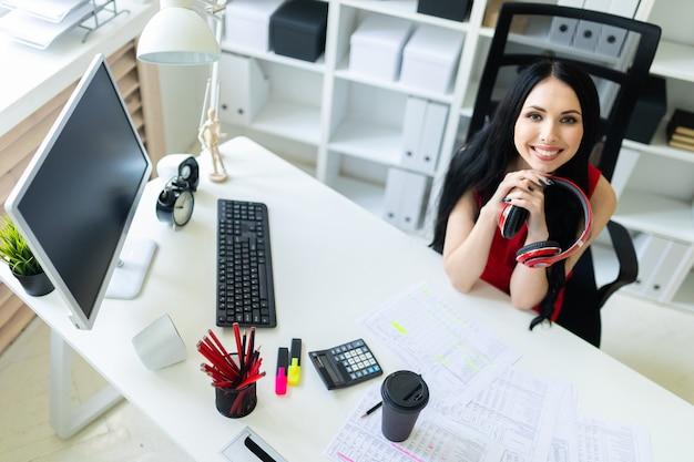 Schönes junges mädchen mit kopfhörern in den händen sitzt im büro am tisch