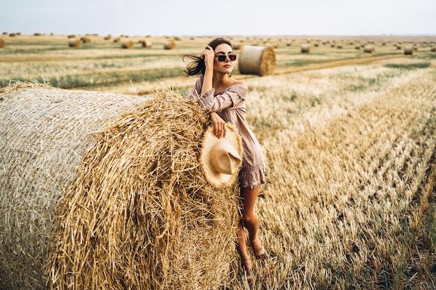 Schönes junges mädchen mit langen haaren in sonnenbrillen und strohhut, die auf einem weizenfeld nahe heuballen aufwerfen. glückliche brünette im sommerkleid