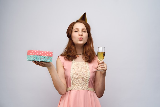 Schönes junges mädchen mit langen roten haaren, die ein glas champagner und schachtelgeschenk halten. sie kniff die augen zusammen und schickte einen kuss