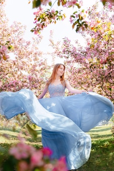 Schönes junges mädchen mit langen roten haaren in einem blauen ballkleid in einem blühenden apfelgarten das konzept der frühlingsblüte und weiblichkeit