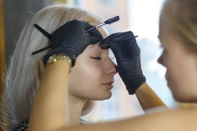 Schönes junges mädchen mit langen wimpern, die ihre augenbrauen in einem schönheitssalon zupfen. augenbrauenkorrektur. schönheitskonzept. dauerhaftes make-up. microblading-braue. kosmetikerin macht augenbrauen