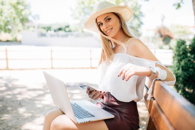 Schönes junges mädchen mit laptop im sommerpark