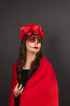 Schönes junges mädchen mit make-up dia de los muertos bedeckt mit einem roten umhang mit grauem hintergrund.
