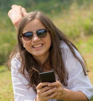 Schönes junges mädchen mit sonnenbrille benutzt den smartphone