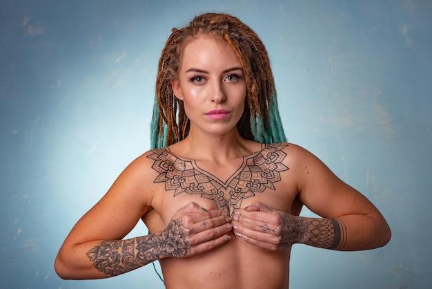 Schönes junges mädchen mit tattoo und dreadlocks posiert oben ohne