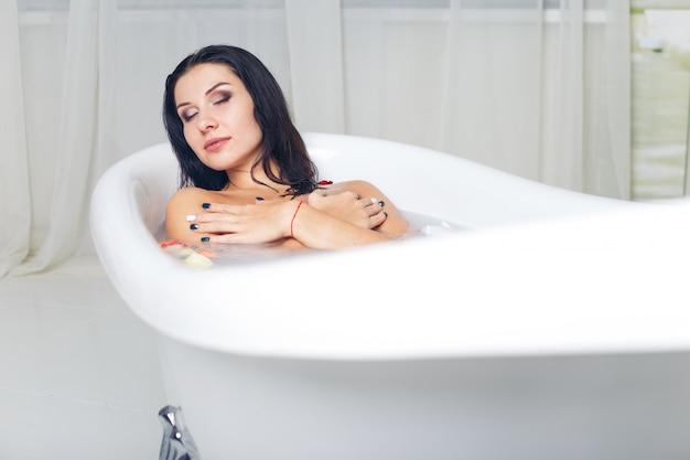 Schönes junges mädchen nimmt bad mit milch