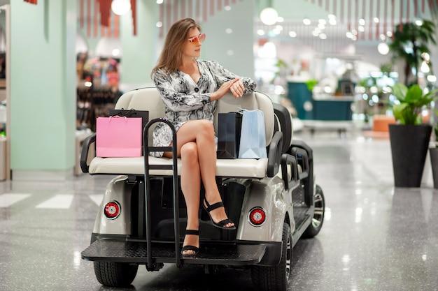 Schönes junges mädchen posiert beim sitzen mit einkaufstüten, die auf einem autositz stehen, um leute zu einem einkaufszentrum zu transportieren. sie schaut auf ihre uhr und überprüft die zeit. tag der rabatte.