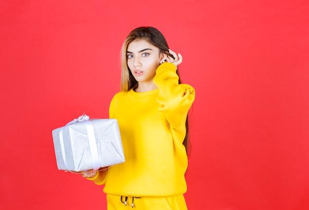 Schönes junges mädchen posiert mit geschenkbox auf roter wand