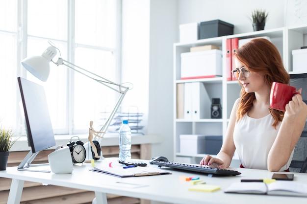 Schönes junges mädchen sitzt am schreibtisch im büro, hält eine schale in einer hand und arbeitet am computer.