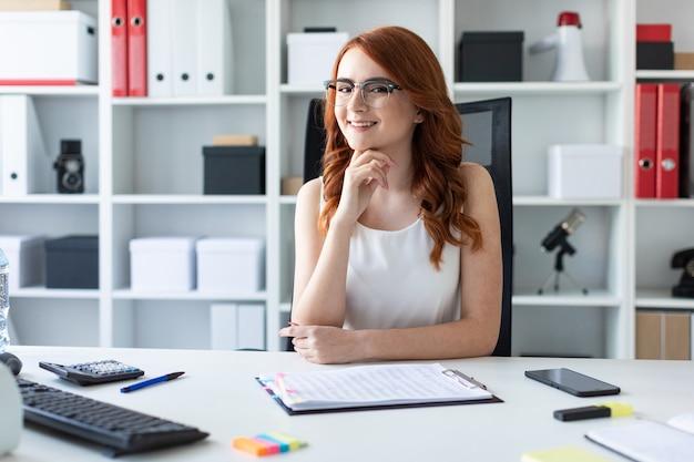 Schönes junges mädchen sitzt am schreibtisch im büro.