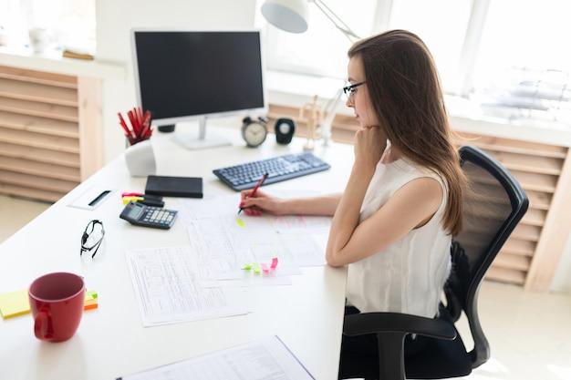 Schönes junges mädchen sitzt am tisch im büro, hält einen stift in ihrer hand und ergänzt die dokumente.