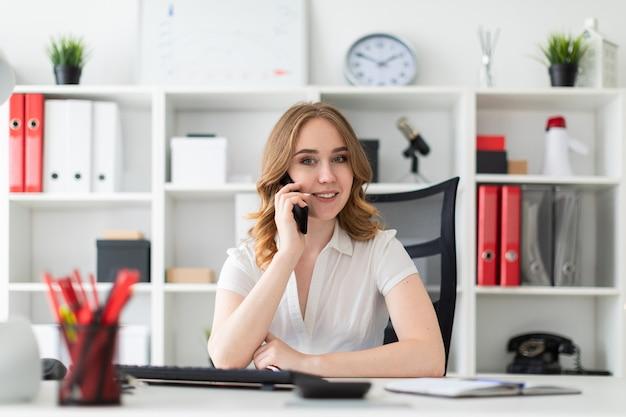 Schönes junges mädchen sitzt im büro und spricht am telefon.