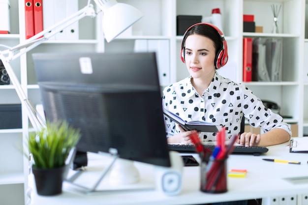Schönes junges mädchen sitzt in den kopfhörern am schreibtisch im büro, hält ein notizbuch in ihrer hand und druckt auf der tastatur. foto mit schärfentiefe, fokus auf mädchen.