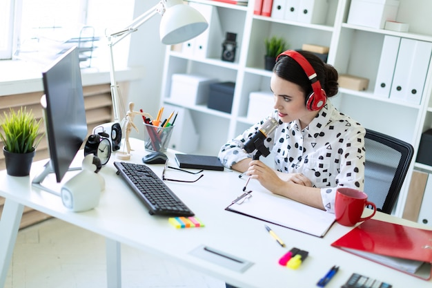 Schönes junges mädchen sitzt in den kopfhörern und mit einem mikrofon am schreibtisch im büro.