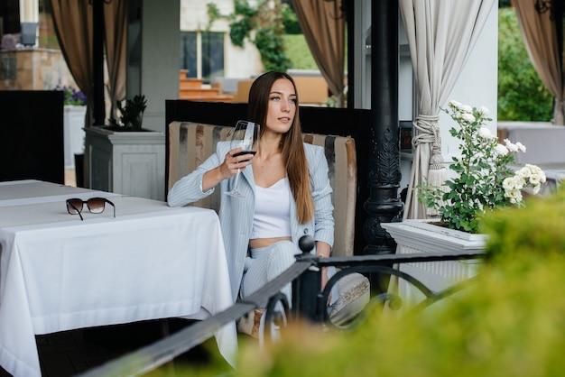 Schönes junges mädchen sitzt und trinkt wein auf der veranda eines schönen hauses. urlaub.