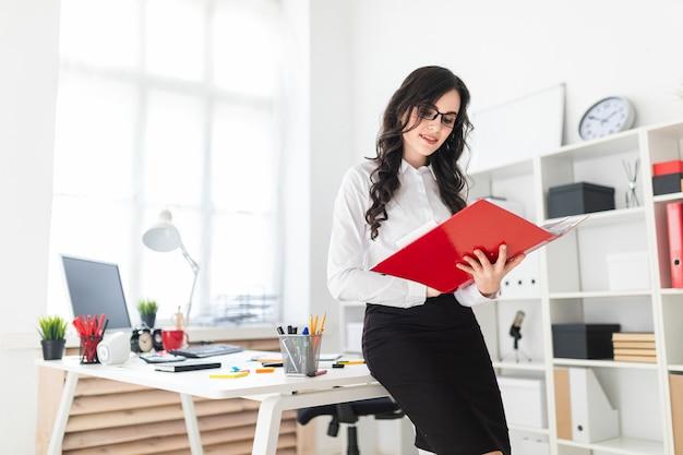 Schönes junges mädchen steht im büro und lehnt sich auf schreibtisch und rollt durch roten ordner mit dokumenten