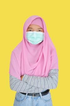 Schönes junges mädchen trägt rosa hijab und maske auf gelbem hintergrund