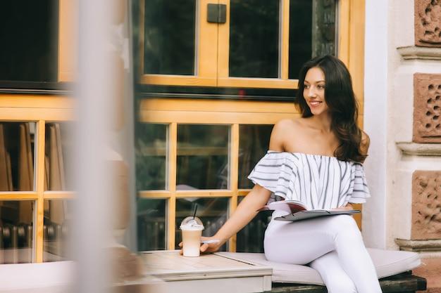 Schönes junges mädchen, trinken kaffee in der stadt