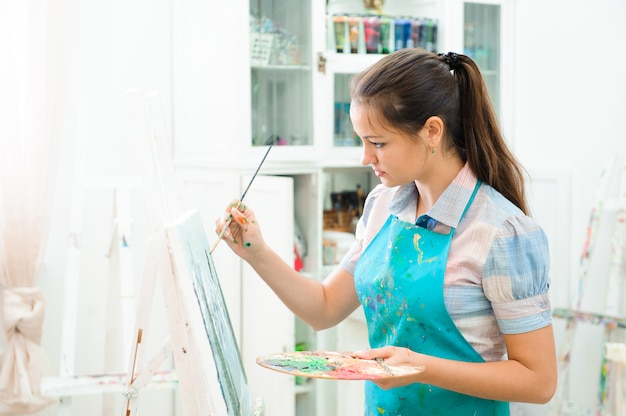 Schönes junges mädchen zeichnet ein bild malt auf kunststunde
